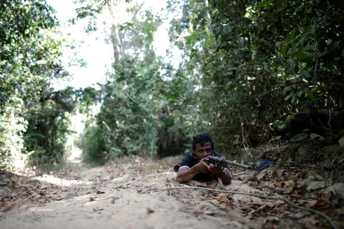 Guajajara wields a rifle during a search for illegal loggers in September. (Ueslei Marcelino/Reuters)