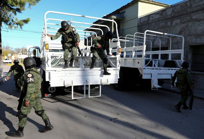 National Guard soldiers arrive Monday in Villa Union, Mexico. The small town near the U.S.-Mexico border began cleaning up Monday even as fear persisted after a deadly gun battle erupted between a heavily armed drug cartel assault group and security forces. (Eduardo Verdugo/AP)