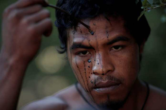 """Paulo Paulino Guajajara, an indigenous """"guardian of the forest"""" seen painting his face in September, was hunting inside the Arariboia reservation in Maranhao state Friday when he was attacked and killed by illegal loggers. (Ueslei Marcelino/Reuters)"""