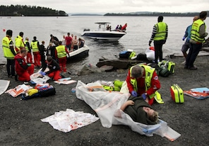 A wounded woman is brought ashore. (Getty Images)