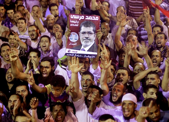 Amr Nabil/AP - Supporters of Egypt's ousted President Mohammed Morsi chant slogans as they hold his poster, in a park near Cairo University, late Monday. The protest turned violent in downtown Cairo as police fired tear gas at pro-Morsi protesters who burned tires, threw rocks and blocked traffic.