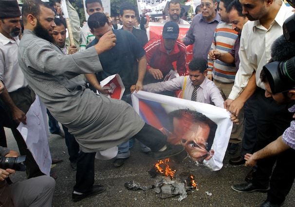 Syrian Protesters kicking and burning Assad's photo