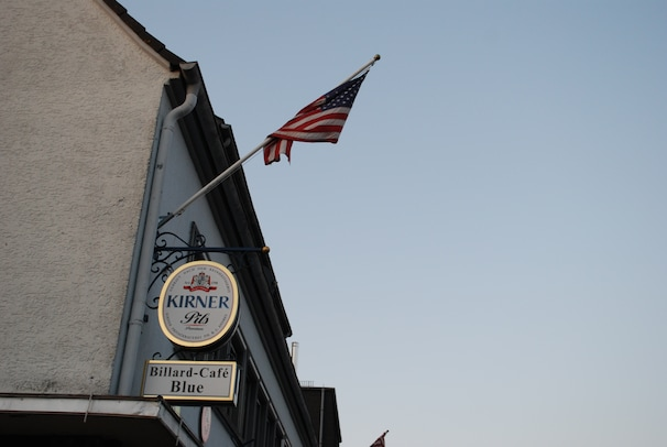 (Michael Birnbaum/ The Washington Post ) - An American flag flies off a German bar in Baumholder, Germany, where 4,500 Germans are surrounded by 13,500 Americans on a U.S. Army base slated for cutbacks. Many of Baumholder's German residents fear that a base closure would radically change their town's character and economic livelihood.