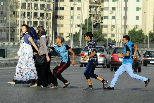 (Ahmed Abdelatif/ AP ) - In this Monday, Aug. 20, 2012 photo, an Egyptian youth, trailed by his friends, grabs a woman crossing the street with her friends in Cairo, Egypt. Several youth groups and activists have held protests and sit ins against sexual harassment, particularly during Muslims holidays which witness a surge of mobs of teenagers sexually harassing women in groups, in the streets.