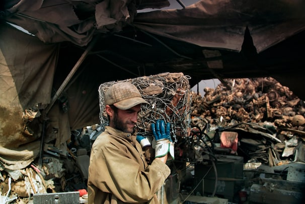 A man collects a block of compressed wires, used to build walls around military bases, from a scrap yard near Bagram. The military has contracted local farmers and other Afghans to haul away the scrap, which is then sold by the contractors.