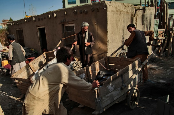 Men push a cart filled with refrigerator parts in Kabul. The U.S. military's decision to cut up its leftovers into scrap does not sit well with many Afghans.