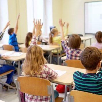group-of-school-kids-raising-hands-in-classroom-PF36XQ9