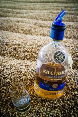 A bottle and a glass of KIlchoman whisky in a pile of barley.