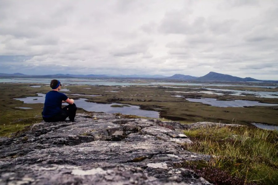 Day 4 Girl sitting at the top of Ruaval on Benbecula - Hebridean Way in 12 days