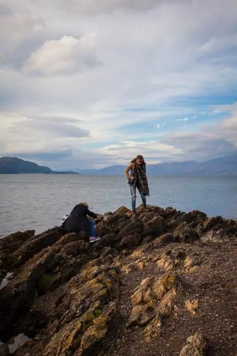 Two people standing by the sea with mountains in the background.