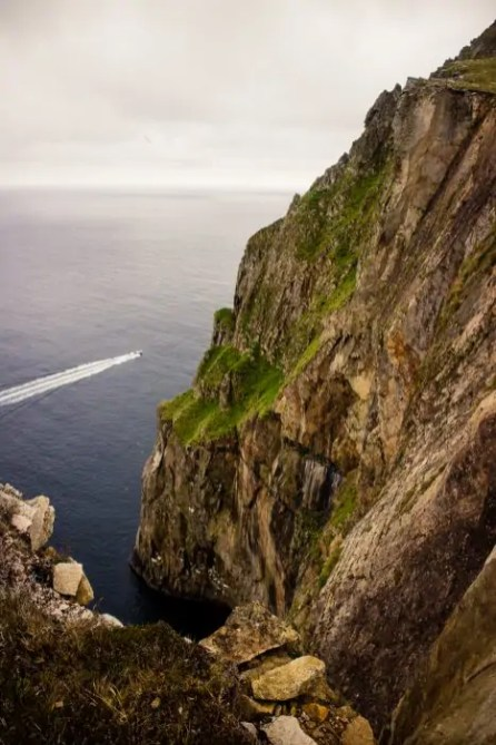 A boat driving around the sea cliffs of St Kilda.