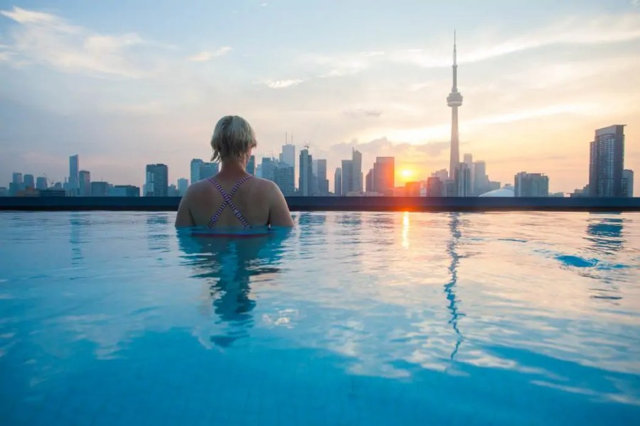 Girl watches sunrise from infinity pool on Thompson Toronto hotel in Toronto.