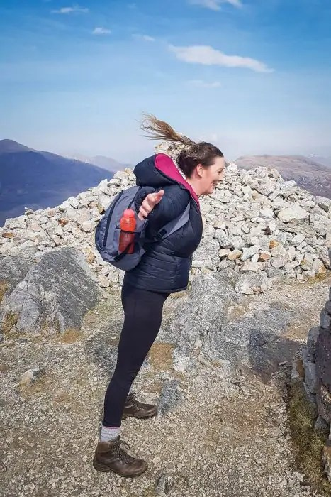 A woman leaning into the wind on a rocky mountain.