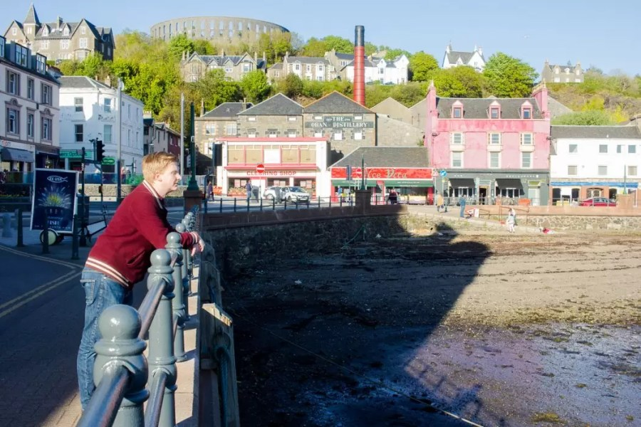 A man standing in front of the skyline of Oban