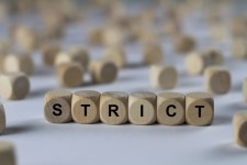 "Wooden cubes spelling out ""strict"""