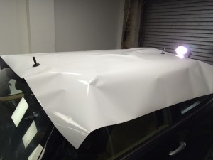 Placed the Vinyl Wrap on the roof, held by magnets ready to be cut to size.