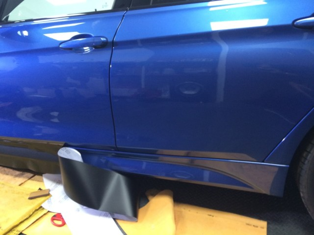 Applied the first half of the side skirt to the car, getting ready to remove the 2nd part of the vinyl