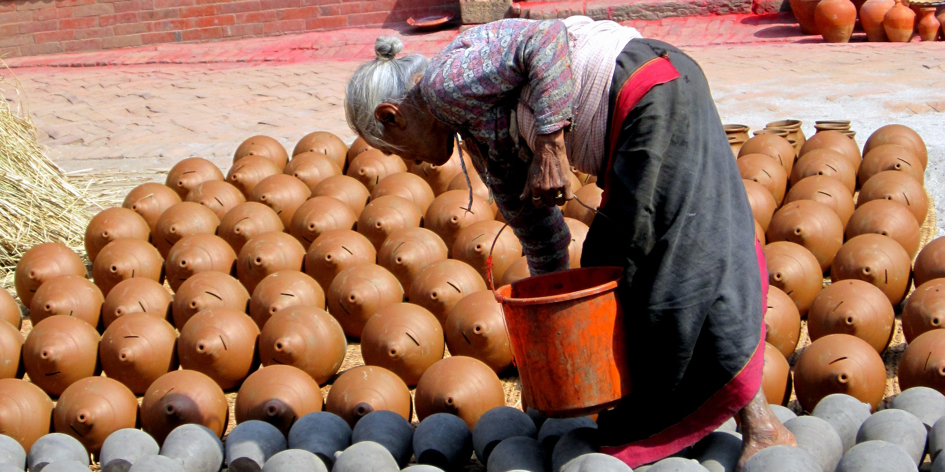 An elderly Newar lady working pottery.