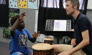 a teacher and indigenous student playing a hand drum