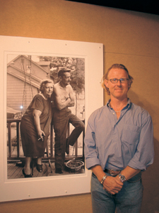photo by Cindy Cornwell Pulitzer Prize-winning photographer and filmmaker, David Turnley, during the opening of the St. Francis exhibition.  (background) Photo of McClellan Street couple on their back porch, behind the old post office in Fort Wayne, was taken during David's high school days at Elmhurst.