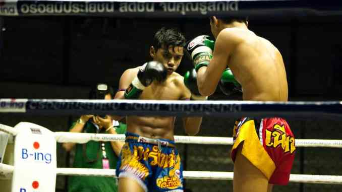 Two Muay Thai boxers fighting in Rajadamnern Stadium, Bangkok, Thailand