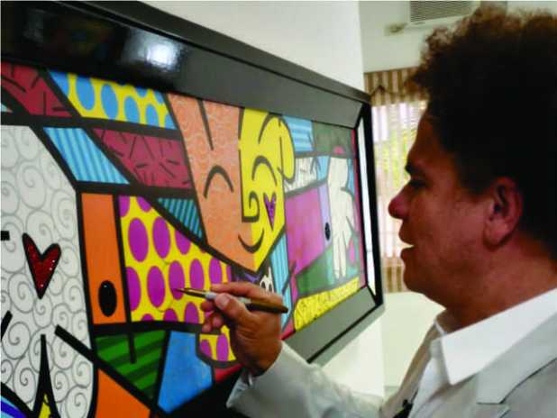 "Neo-pop artist Romero Britto signs his famous artwork ""The Hug"""