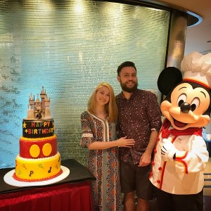 "alt=""Daniel, his fiance, and Mickey pose for a picture at Chef Mickey restaurant at the Hong Kong Disneyland Resort."""