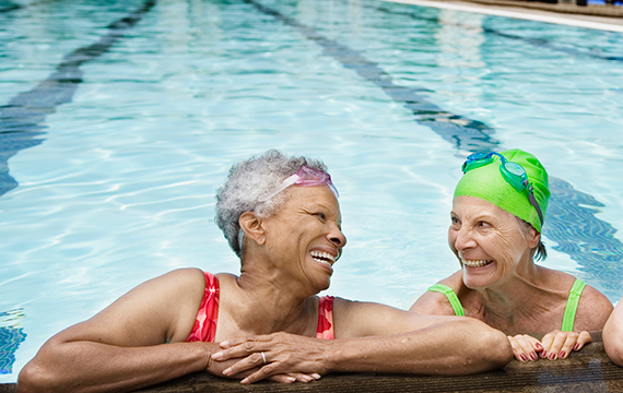 two senior women swimming by the pool