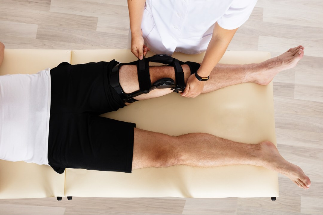 physiotherapist fits a brace onto the patient's knee on a bed