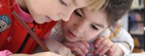 two children writing in school