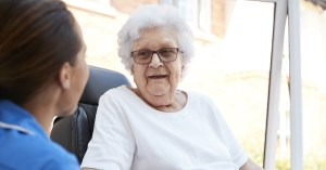 Image shows care home resident talking to a member of staff