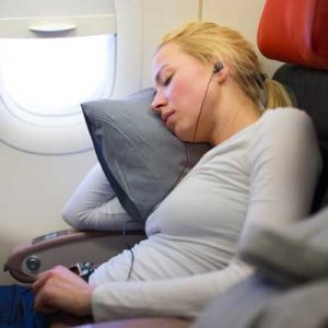 woman sleeping on flight with earbuds