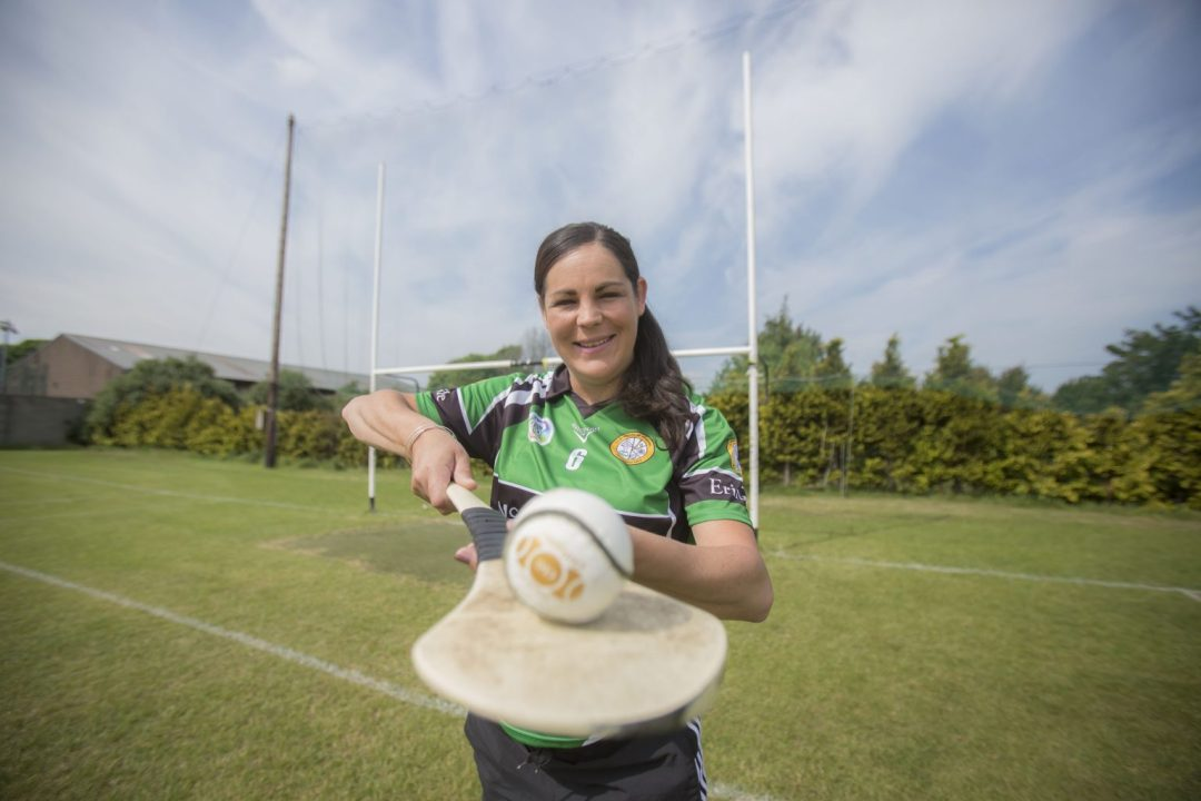 Louise O'Hara in a green with black band on sleeves and across the front middle Erin's Isle jersey pointing a hurl with a white ball balanced on it at the camera lens