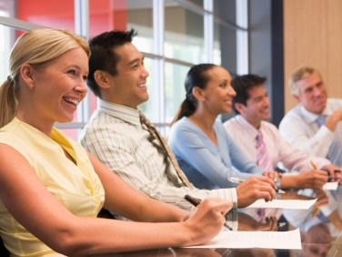 Five businesspeople at boardroom table smiling
