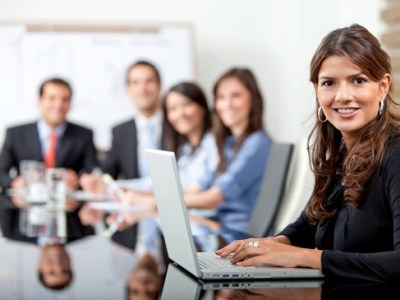 Senior board level woman on laptop in meeting