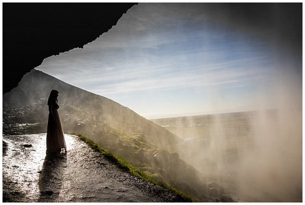 Anna stands behind Seljalandsfoss waterfall in Iceland