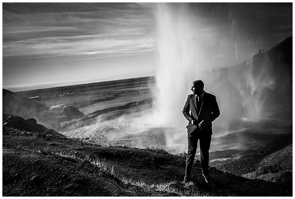 A black and white image of Mike standing behind Seljalandsfoss waterfall in Iceland