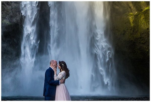 Mike and Anna kiss in front of Skogafoss Waterfall in Iceland