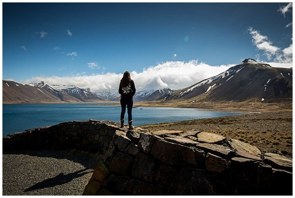 Anna stands on a rock wall and looks out at the fjords in Iceland
