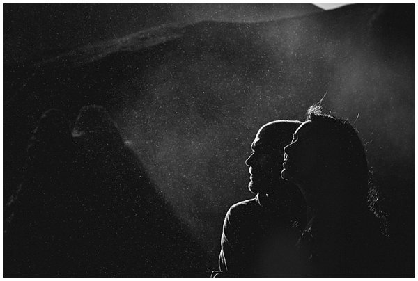 The sun creates silhouettes of Anna & Mike's profiles in the spray of the waterfall