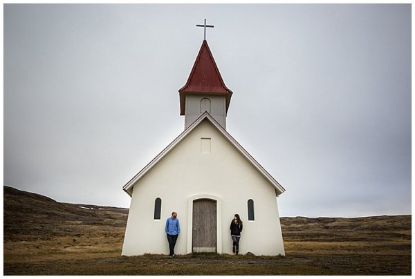 Iceland Anna and Mike lean either side of the front door of a red and white church in Iceland