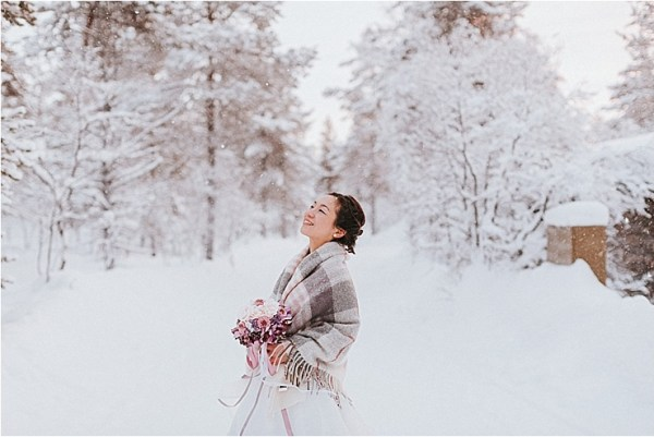 The bride looks up to the trees as snow falls down around her by Maria Hedengren Photography