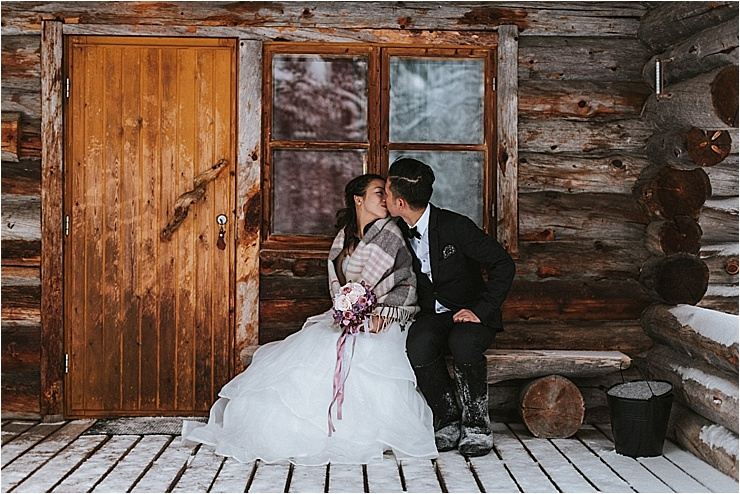 The bride and groom sit on a wooden bench outside a log cabin in Finland by Maria Hedengren Photography