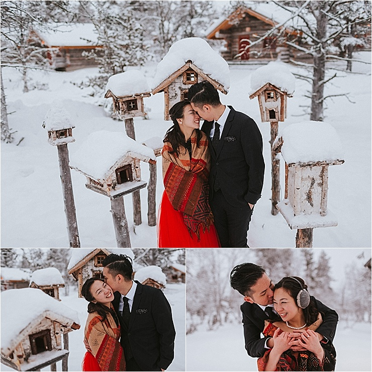 Bride and groom smile and laugh while they embrace standing in the snow in Finland with wooden bird houses surrounding them and the bride wears a red dress by Maria Hedengren Photography