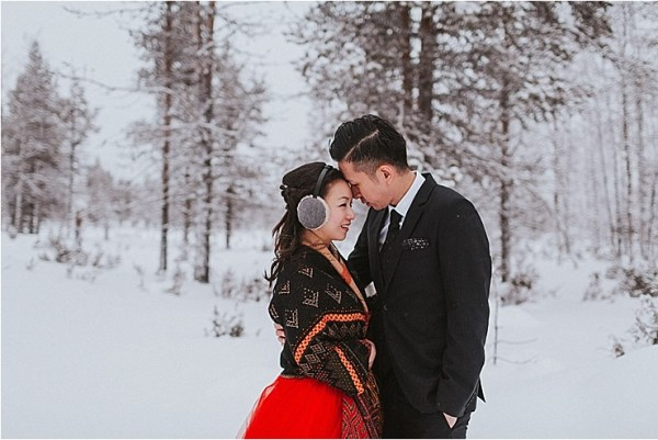 The bride and groom embrace with their heads together whilst standing in the snowy forest in Lapland by Maria Hedengren Photography