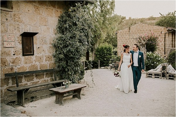 The bride and groom walk around the outside of Borgo di Tragliata while the groom puts his arm around his bride by Michele Abriola