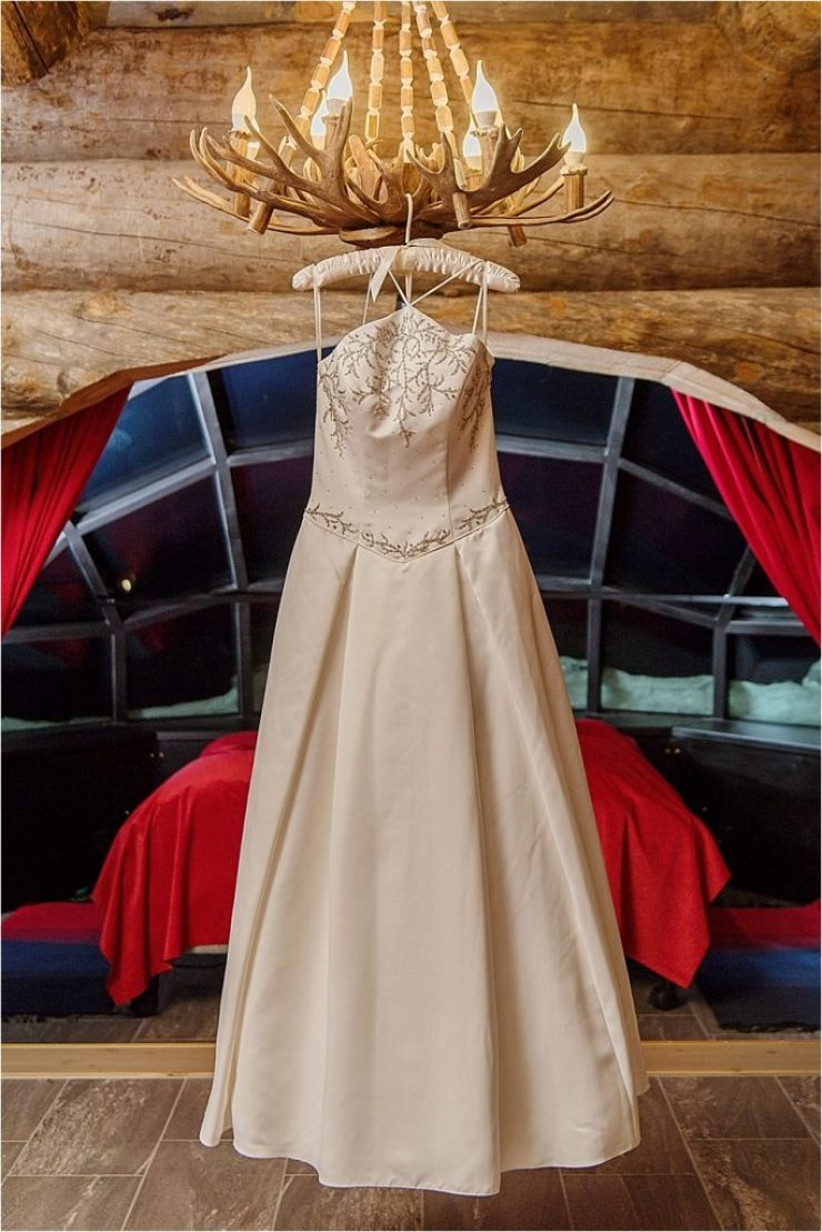 The wedding dress hangs in the bridal suite at Kakslauttanen arctic resort in Finland by Your Adventure Wedding