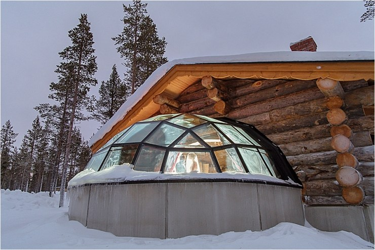 A view of the bride getting ready in her glass igloo taken from outside at the Kakslauttanen arctic resort in Finland by Your Adventure Wedding
