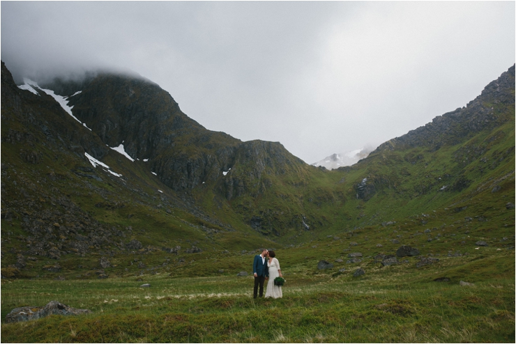 A portrait of the bride and groom among the green mountains in Lofoten Norway by Thomas Stewart