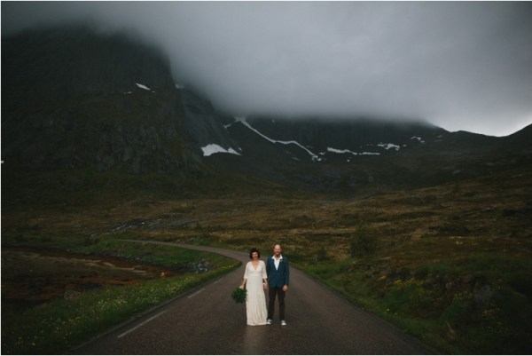 Bride and groom stand on an empty road in Lofoten Norway by Thomas Stewart